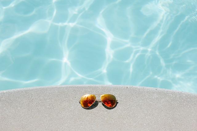 sluneční brýle na okraji bazénu